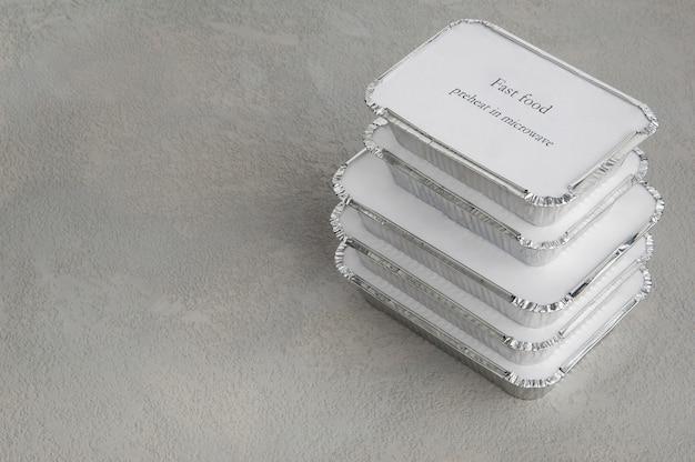 Ensemble de restauration rapide dans une boîte de papier d'aluminium sur un fond gris rugueux. nourriture pour homme d'affaires et personnes occupées