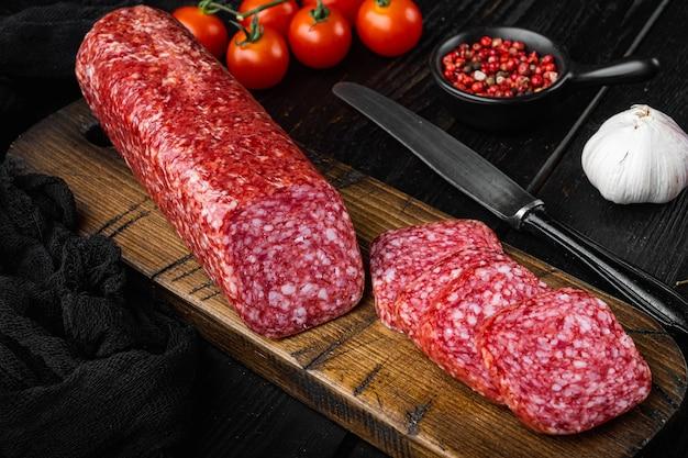 Ensemble de romarin et d'épices frais de saucisse, sur la table en bois noire