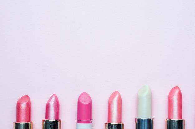 Ensemble de rouges à lèvres roses sur fond rose. produits de beauté pour femmes. mise au point sélective. espace de copie.