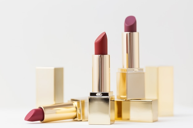 Ensemble de rouges à lèvres rouges dans des étuis dorés sur fond blanc. maquillage