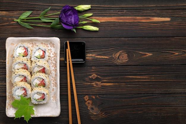 Ensemble de rouleaux de sushi avec du riz au fromage à la crème et du saumon sur une planche décorée de gingembre sur un bois