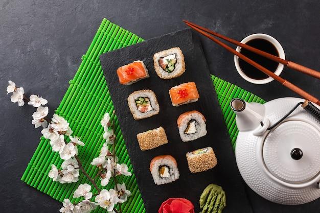 Ensemble de rouleaux de sushi et maki avec branche de fleurs blanches et théière avec l'inscription thé vert sur table en pierre. vue de dessus.