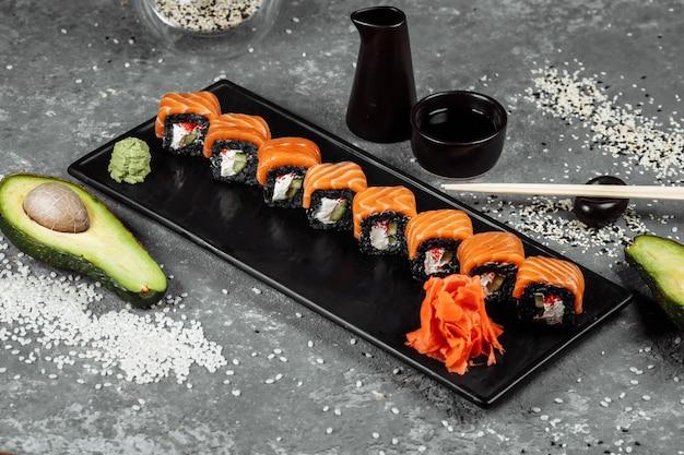 Un ensemble de rouleaux de sushi philadelphie avec du poisson rouge, du fromage à la crème et de la montée noire se trouve dans une assiette en bateau