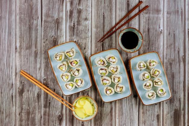 Ensemble de rouleaux de sushi avec sauce soja, gingembre et baguettes cuisine asiatique
