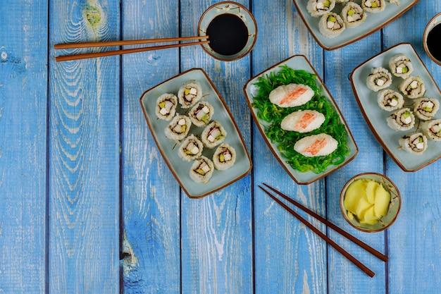 Ensemble de rouleaux de sushi avec sauce soja, gingembre et baguettes cuisine japonaise