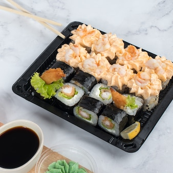 Ensemble de rouleaux de sushi servi sur planche de bois sombre avec wasabi, sauce soja et gingembre.