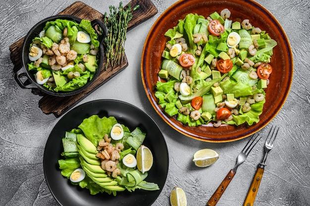 Ensemble de salades avec avocat, crevettes, crevettes et verts dans des bols. vue de dessus.
