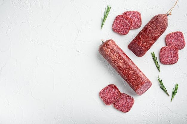 Ensemble de salami aux herbes et épices, sur table en pierre blanche