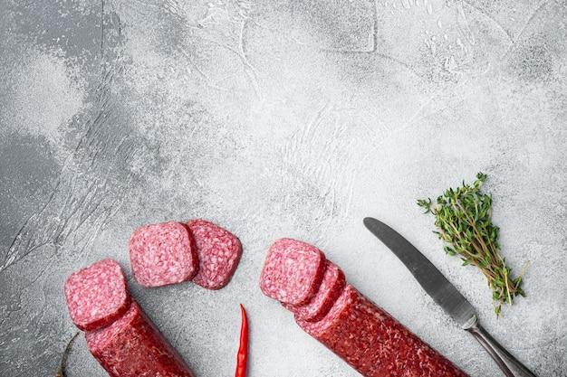 Ensemble de salami aux herbes et épices, sur table en pierre grise