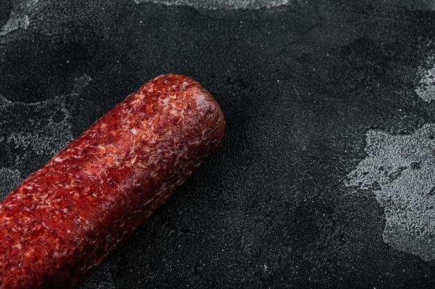 Ensemble de salami de saucisses fraîches au four, sur fond noir en pierre sombre, avec espace de copie pour le texte