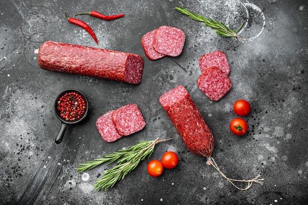 Ensemble de salami tranché, sur fond de table en pierre noire noire, vue de dessus à plat