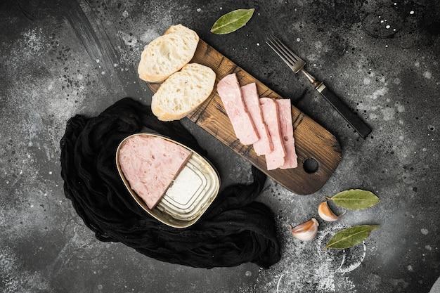 Ensemble de sandwichs au jambon en conserve, sur fond de table en pierre noire noire, vue de dessus à plat