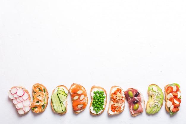 Ensemble de sandwichs colorés préparés avec différents ingrédients tels que du poisson, des légumes et de la viande