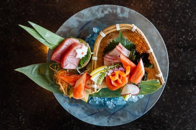 Ensemble de sashimi frais comprenant du thon bleu, du hamachi et du bâton de crabe servis avec du wasabi