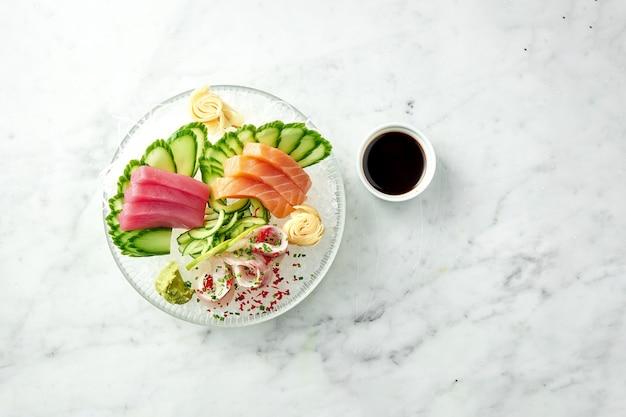 Ensemble de sashimi japonais classique de saumon cru, anguille et thon au citron vert, concombre sur plaque sur une table en marbre. gros plan, mise au point sélective