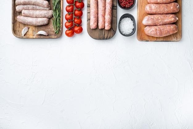 Ensemble de saucisses crues, vue de dessus avec un espace pour le texte, sur fond blanc.