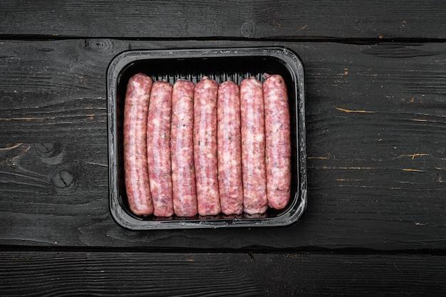 Ensemble de saucisses emballées sous vide, sur fond de table en bois noir, vue de dessus à plat