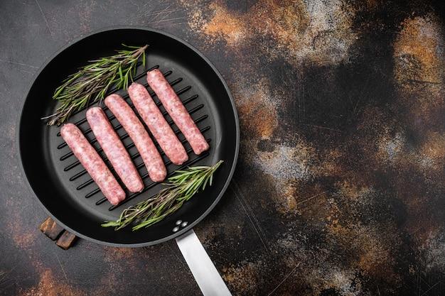 Ensemble de saucisses fraîches faites maison, sur une poêle en fonte à frire, sur un vieux fond de table rustique sombre, vue de dessus à plat, avec espace de copie pour le texte