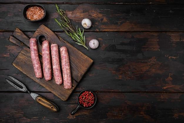 Ensemble de saucisses fraîches faites maison, sur un vieux fond de table en bois foncé, vue de dessus à plat, avec espace de copie pour le texte
