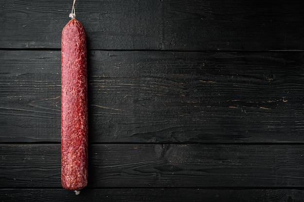 Ensemble de saucisses fumées au salami, sur fond de table en bois noir, vue de dessus à plat, avec espace de copie pour le texte