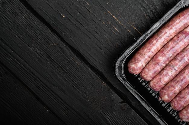 Ensemble de saucisses polonaises fraîches, sur fond de table en bois noir, vue de dessus à plat, avec espace de copie pour le texte