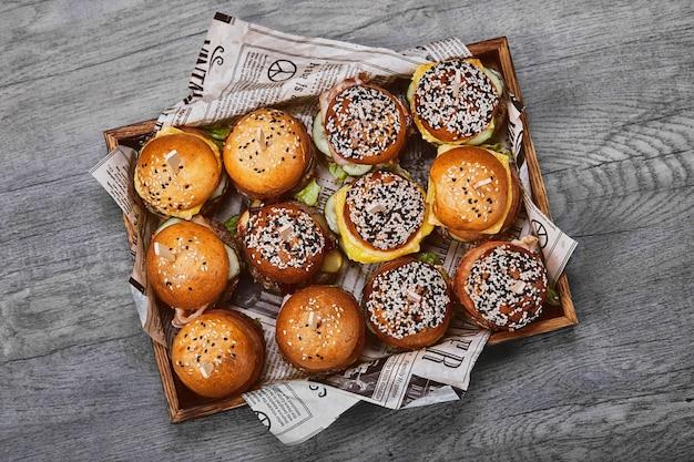 Ensemble de savoureux cheeseburger dans une boîte en bois sur un fond clair. une boîte avec différents burgers, une offre fixe pour une entreprise,