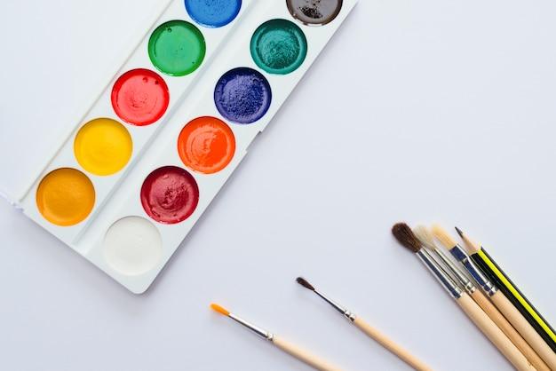 Ensemble scolaire d'aquarelles, pinceaux et crayons sur papier blanc