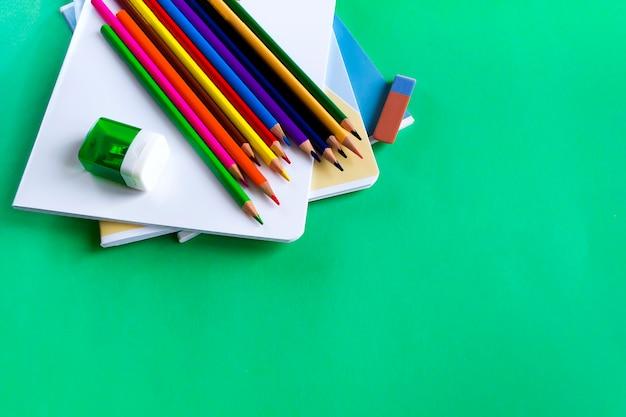 Ensemble scolaire de cahiers, crayons, une gomme à effacer et des taille-crayons sur fond vert