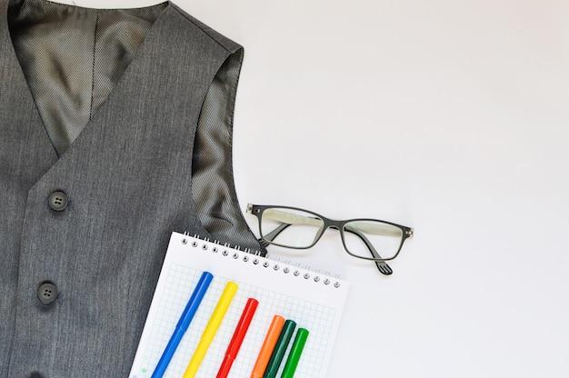 Ensemble scolaire avec gilet, crayons, feutres et lunettes sur fond blanc.
