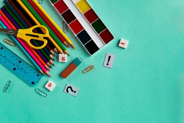 Ensemble scolaire de peintures, crayons, règles. plastique et chiffres sur un fond de papier vert avec espace de copie. pose à plat