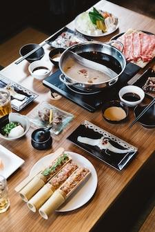 Ensemble shabu comprenant des tranches rares de bœuf wagyu a5, shabu shoyu et base claire, saumon, sushi.