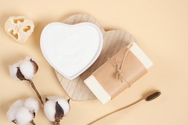Ensemble de soins corporels écologiques, savon, soda, luffa et fleur de coton sur fond beige, brosse à dents en bambou. concept de mode de vie zéro déchet, espace de copie de vue de dessus de cosmétiques naturels