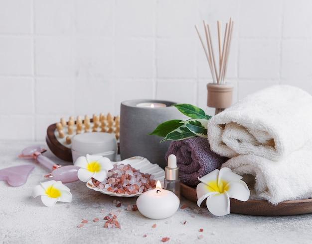 Ensemble de spa, huile essentielle, sel de massage, bougie et fleurs de frangipanier sur fond de béton gris