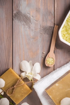 Ensemble de spa. savon organique fait main et naturel et orchidée blanche sur un fond en bois