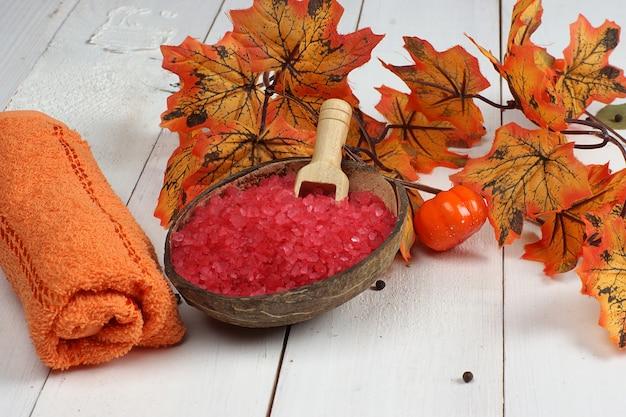 Ensemble de spa de sel de bain et de serviettes sur une table en bois blanc et près de feuilles d'érable d'automne orange
