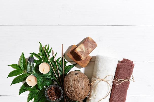 Ensemble de spa avec serviette et savon sur fond de bois blanc avec des feuilles vertes