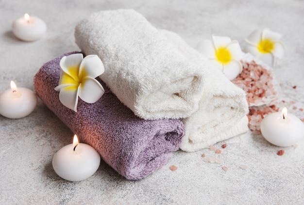 Ensemble de spa, serviettes, sel de massage, bougie et fleurs de frangipanier sur fond de béton gris