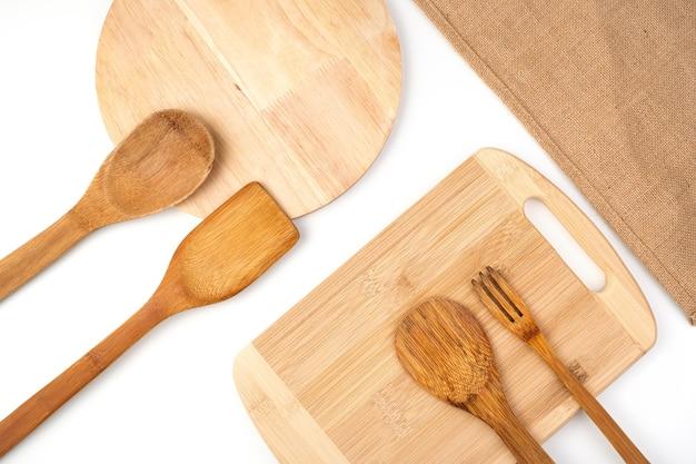 Un ensemble de spatules en bois, des planches à découper et une serviette en lin sur fond clair. vue de dessus avec