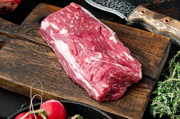 Ensemble de steak d'angus noir de viande marbrée fraîche crue, filet mignon de filet mignon coupé, sur une planche à découper en bois, sur une table en pierre noire