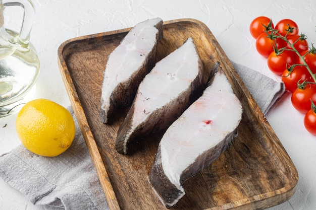 Ensemble de steak de poisson cru, avec des ingrédients et des herbes de romarin, sur fond de table en pierre blanche