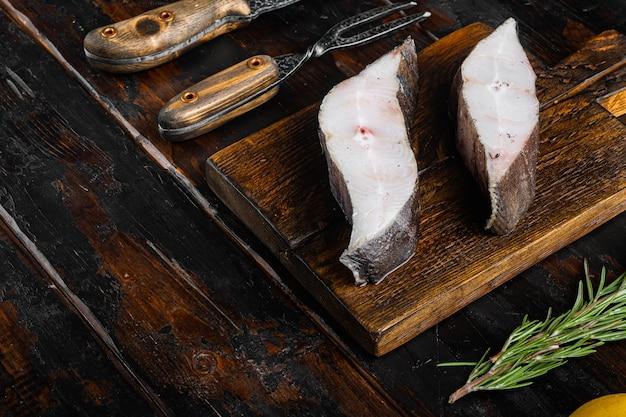 Ensemble de steak de poisson cru, avec des ingrédients et des herbes de romarin, sur un vieux fond de table en bois sombre, avec un espace de copie pour le texte