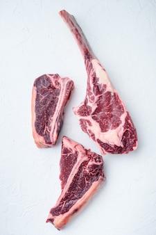Ensemble de steak de viande de boeuf porterhouse cru à sec, tomahawk, t bone ou porterhouse et club steak, sur table en pierre blanche, vue de dessus à plat