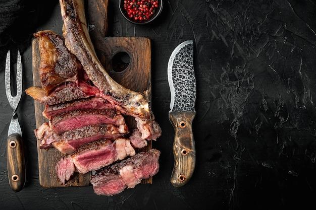 Ensemble de steaks de boeuf tomahawk tranchés grillés, sur une planche de service en bois, sur fond de pierre noire, vue de dessus à plat