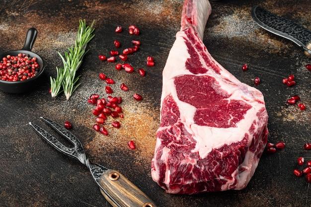 Ensemble de steaks de côtelettes de boeuf tomahawk black angus prime cru frais, avec assaisonnement et herbes, sur une vieille table rustique sombre