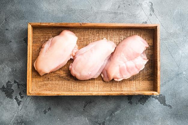 Ensemble de steaks de filet de poulet coupé en tranches crues fraîches, dans une boîte en bois, sur pierre grise
