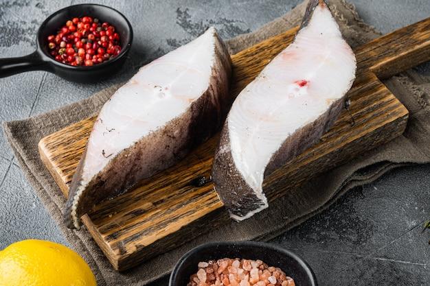 Ensemble de steaks de flétan réfrigérés, avec ingrédients et herbes de romarin, sur fond de table en pierre grise