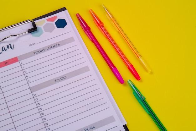 Ensemble de stylos et calendrier hebdomadaire sur fond jaune. concept de planification de mois de vue de dessus.