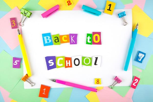 Ensemble de stylos colorés, notes autocollantes, blocs-notes, stylos, pinces à relier. vue de dessus. retour à l'école