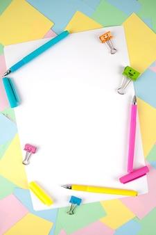 Ensemble de stylos colorés, notes autocollantes, blocs-notes, stylos, pinces à relier. vue de dessus