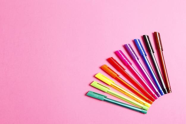 Ensemble de stylos multicolores sur fond rose. place pour le texte. vue de dessus.